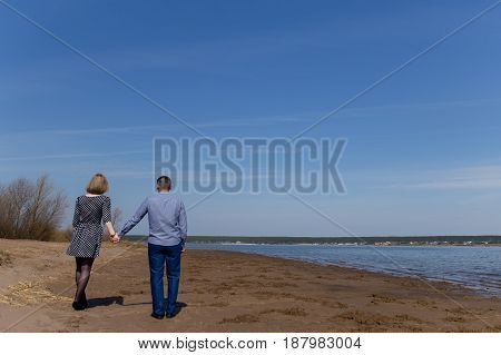Full Length Rear View Of A Couple Walking Hand In Hand At Beach