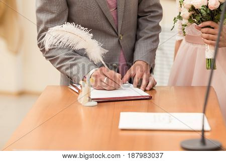Bride And Bridegroom Signing The Marriage Contract After The Wedding Ceremony