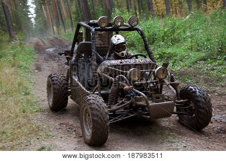 Horizontal outdoors shot of man driving a buggy car in mud.