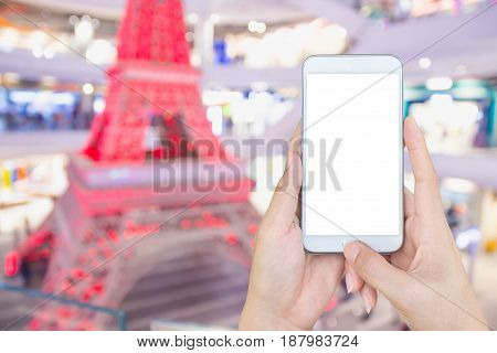 Hand holding smart phone with abstract blur in shopping mall background