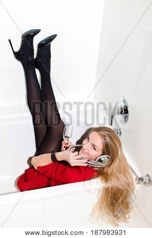 Vertical indoors shot of pretty woman lying in bath with sham and using shower as a phone.