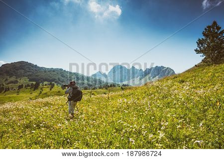 Photographer taking photos in mountain in summertime. Intentionally toned.