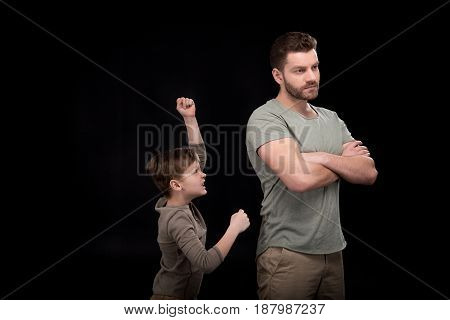 Father Standing With Crossed Arms And Little Son Quarreling And Gesturing, Family Problems Concept