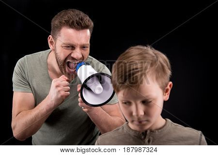 Father With Megaphone Screaming At Scared Little Son, Family Problems Concept