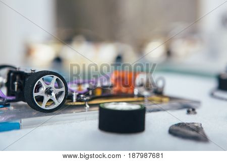 Close-up wheels and different parts of handcrafted miniature auto toy.