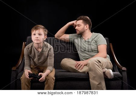 Upset Father Sitting On Sofa Near Little Son Playing With Joystick, Family Problems Concept