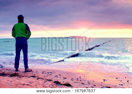 Man Silhouette Stand On Stony Beach And Watching Sunrise