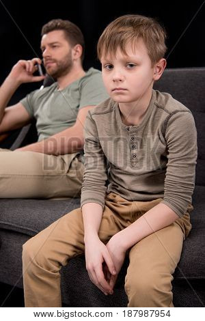 Upset Little Son Sitting On Sofa While Father Talking On Smartphone Behind, Family Problems Concept