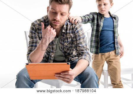 Upset Little Boy Trying To Talk With Father Using Digital Tablet, Family Problems Concept