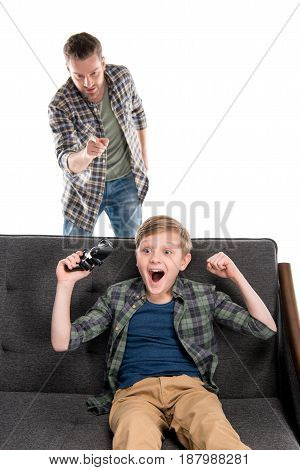 Serious Father Pointing With Finger And Excited Son Sitting On Sofa With Joystick, Family Problems C