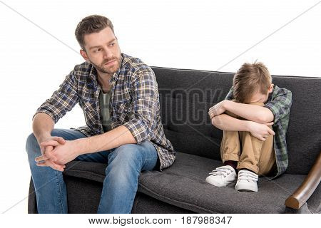 Father Sitting On Sofa Near Scared Little Son, Family Problems Concept