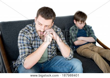 Upset Father And Son Sitting On Sofa After Quarrel, Family Problems Concept