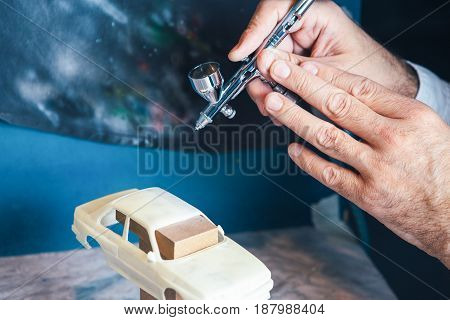 Hands of unrecognizable man using airbrush for painting handcrafted miniature auto.