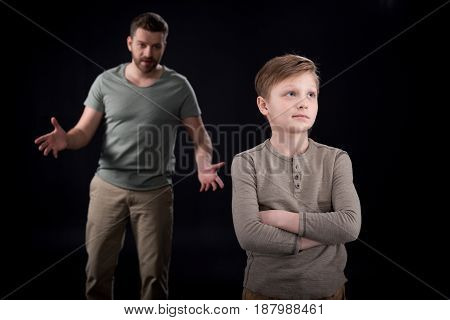 Father Quarreling At Indifferent Son Standing With Crossed Arms, Family Problems Concept