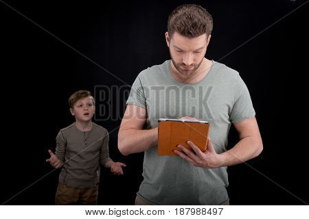 Upset Little Boy Gesturing And Looking At Father Using Digital Tablet, Family Problems Concept