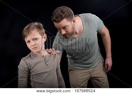 Irritated Father Holding Shoulder Of Scared Little Son, Family Problems Concept