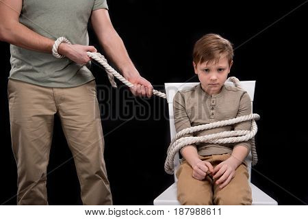 Cropped Shot Of Father With Rope Tied Little Son Sitting On Chair, Family Problems Concept