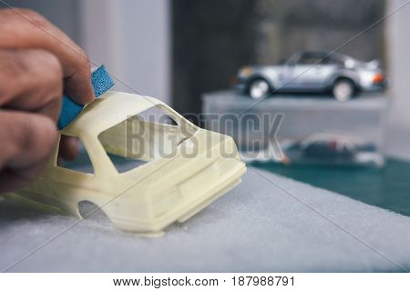 Unrecognizable master handcrafting and polishing small slot car.