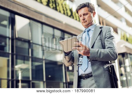 Handsome mature businessman in classic suit using a digital tablet.