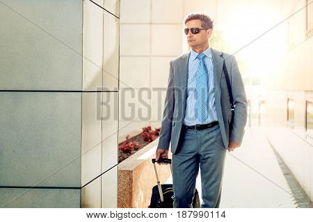 Businessman with luggage on the way to traveling.