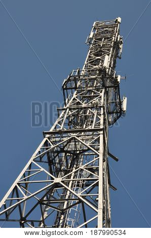 Telecommunication towers with antennas on clear blue sky