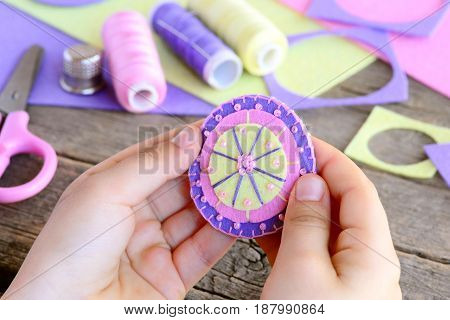 Small child made a beautiful flower from felt circles and beads. Child holds a felt flower in hands. Felt flower DIY, craft supplies on wooden table. Easy and fun sewing. Teaching kids to sew by hand