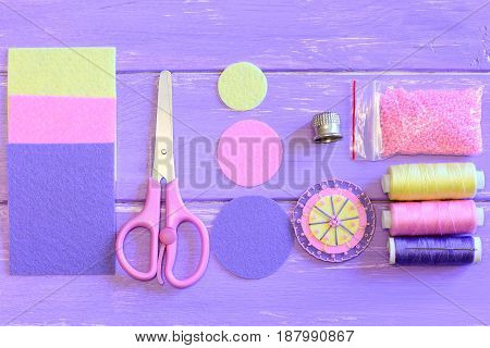 Pretty round flower made of felt and beads, colored felt circles and sheets, scissors, thread spools set, needle, pink beads on a wooden table. Sewing guide. Teaching sewing for children. Top view