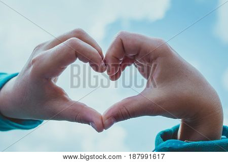 young girl's hands making heart symbol upon the sky