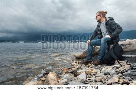 Man traveler with a backpack seets on the seashore against a background of clouds and a mountain range concept of hiking