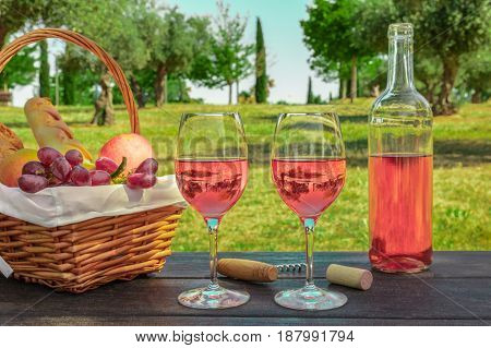 Two glasses of rose wine and a bottle at a picnic, with green grass and trees in the blurred background, with a place for text, slightly toned