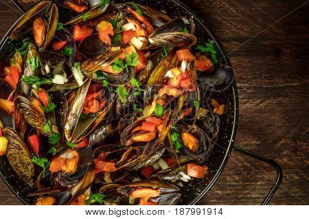 A closeup of a skillet of marinara mussels, shot from above on a dark rustic background with a place for text