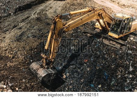 Industrial Excavators Working On Garbage Dump. Heavy Duty Machinery At Work