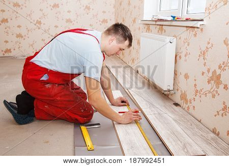 young handyman installing wooden floor in new house