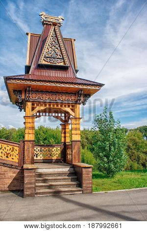 wooden pergola decorated with carvings on sunny summer day