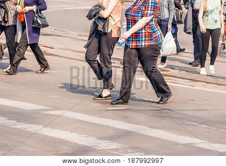 road crossing with women pedestrian feet on sunny spring day