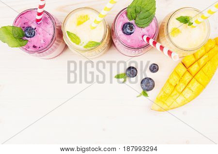 Yellow and violet fruit smoothie in glass jars with straw mint leaves mango slices and berry top view. Soft white wooden board background copy space.