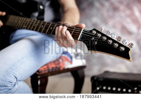 musician playing electric guitar on a dark background