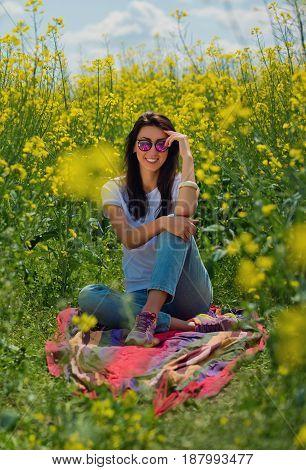 Portrait of lovely brunette in sunglasses sits in rapeseed field. Vertical shot.