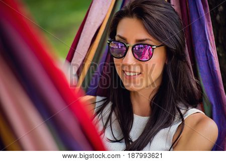 Young lovely brunette in sunglasses is lies in a hammock. Close-up.
