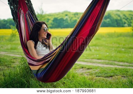 Young brunette girl lies in a hammock and talks on the mobile phone.
