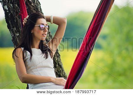 Portrait of lovely brunette girl in sunglasses is lies in a hammock.