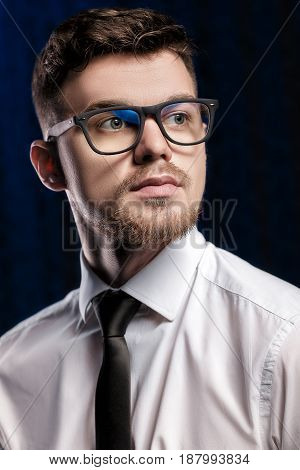Portrait of a handsome young man with glasses and a white shirt on dark background