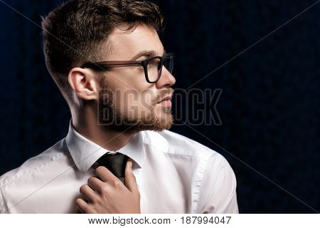 Profile of a handsome young man with glasses and a white shirt on dark background