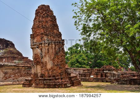 Ruins of stupa and statue of Buddha in Wat Mahathat the ancient Thai temple in Ayutthaya Historical Park. Was built in 1374