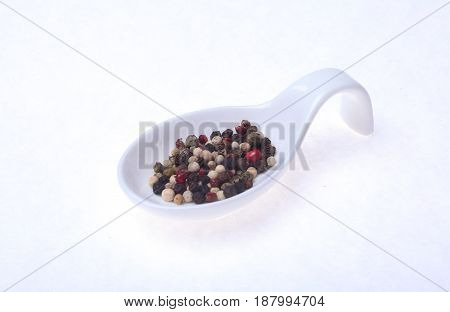 mixed black, white and red pepper corns in bowl isolated on white background
