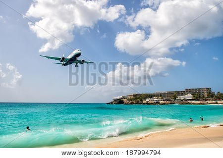 St.Maarten Kingdom of Netherlands - February 13 2016: beach crowds observe low flying airplanes landing near Maho Beach on island of St.Maarten in the Caribbean