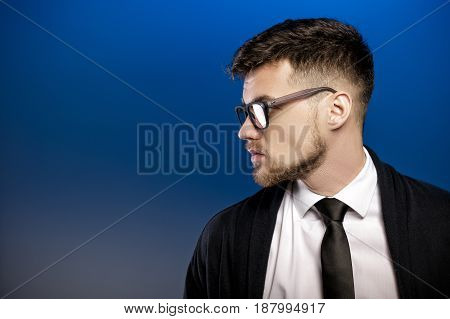 Profile of a handsome young man with glasses and a white shirt on a blue background