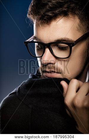 Portrait of a handsome young man with glasses on a blue background