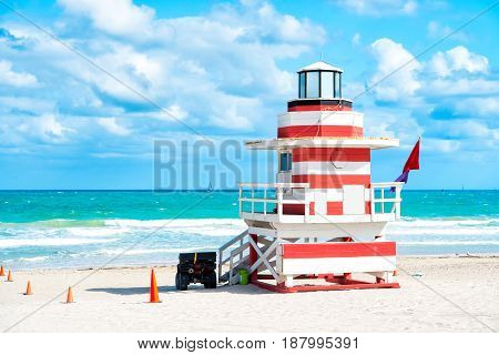 South Beach Miami Florida lifeguard house in a colorful Art Deco red and whhite style on cloudy blue sky and Atlantic Ocean in background world famous travel location