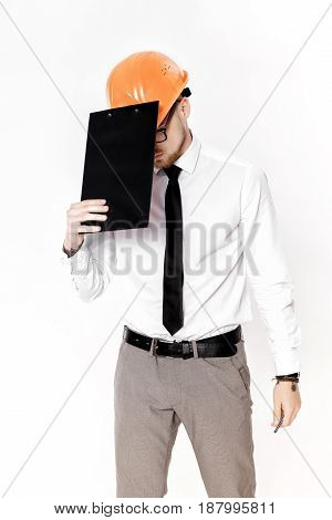 Portrait of young construction engineer in orange helmet with a folder on a white background